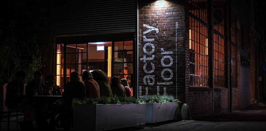 Exterior view of Factory Floor taken in the evening showing customers and the warm interior glow of the venue